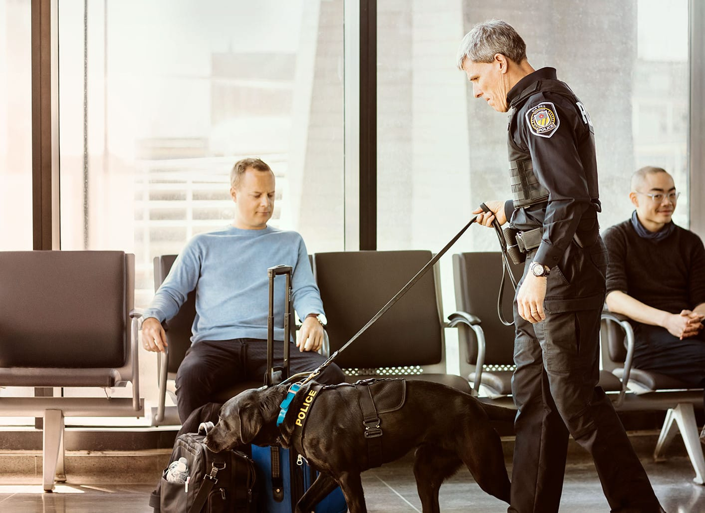 Photo of Police with a dog scaning a man's luggage.