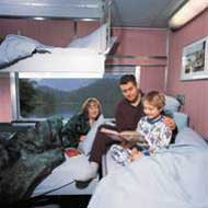 Man reading with his son in a berth of a cabin for 3 in Sleeper class
